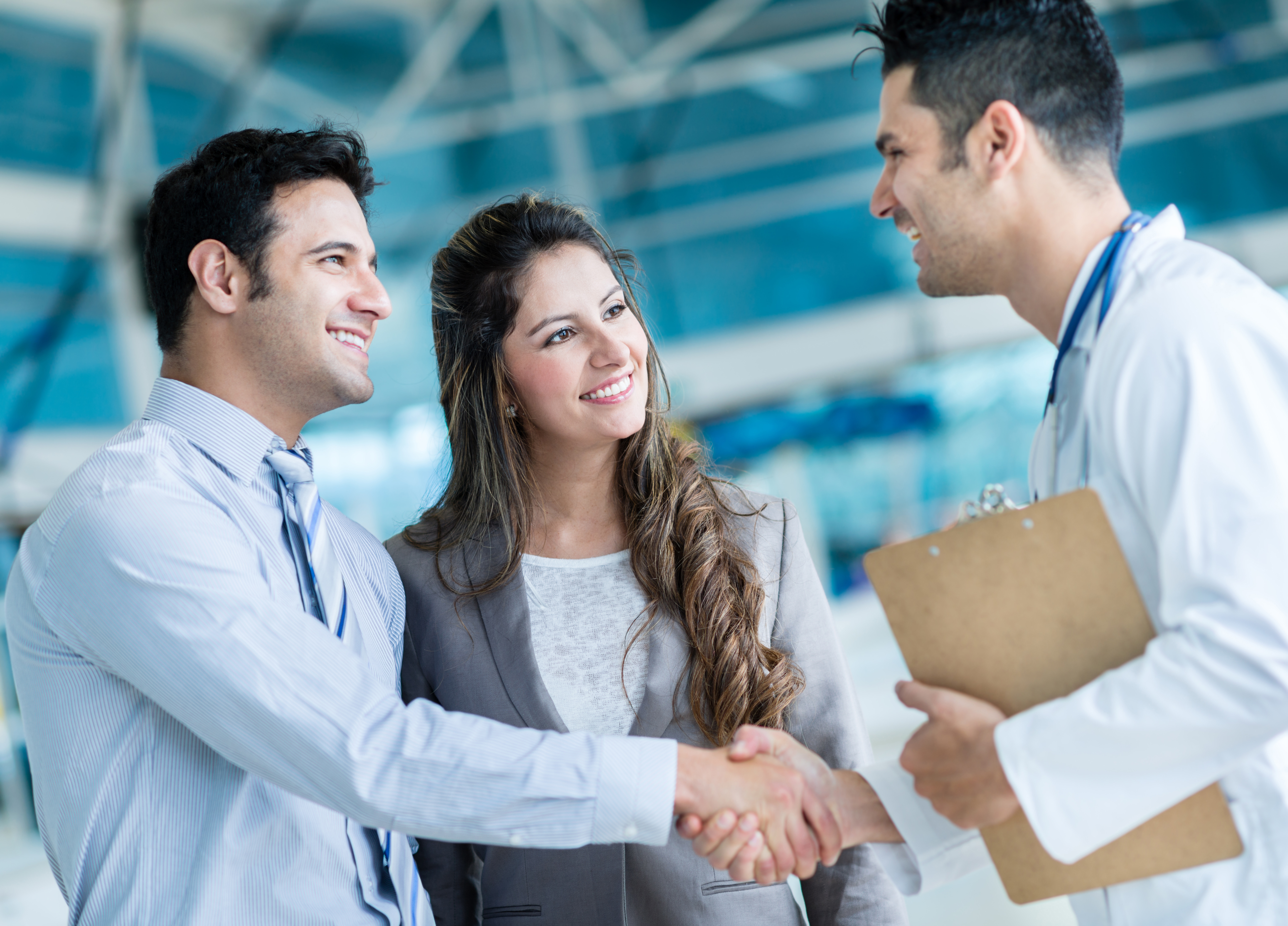 Family doctor handshaking a couple at the hospital