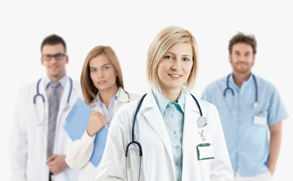 Team of young medical doctors smiling at camera, isolated on white.